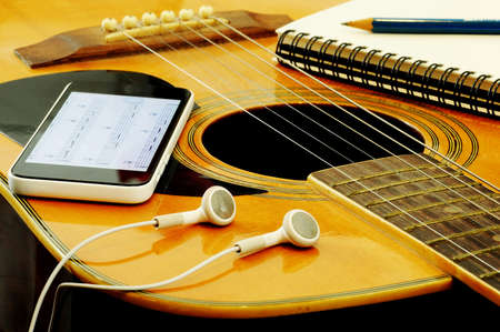 Phone open a note of song with headset notebook and pencil on guitar Foto de archivo