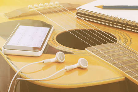 notebook paper: Phone open a note of song with headset notebook and pencil on guitar in vintage tone