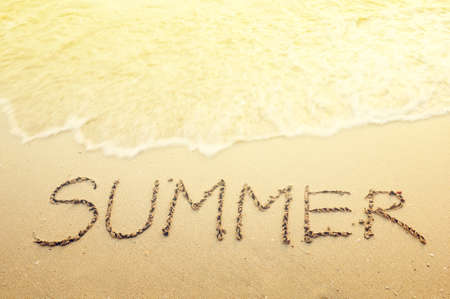 on coming: Handwriting summer on the beach Stock Photo
