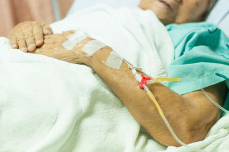 Close up a hand of an old woman patient in hospital with saline intravenous