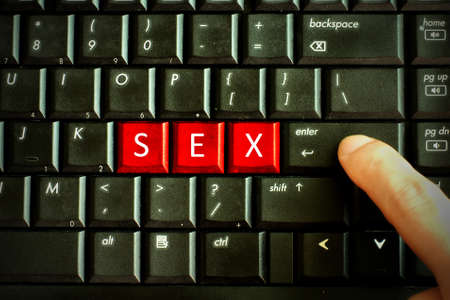 Finger press red button Keywords SEX on keyboard computer, Adult sex online concept 免版税图像