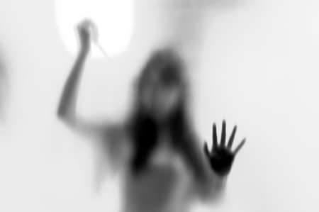 rapist: Shadow woman figure with a  scissors behind glass in black  white