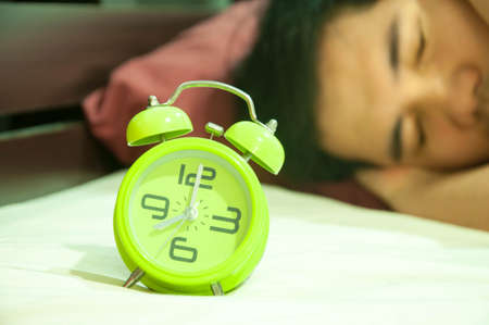 annoyed: Young man was annoyed from alarm clock at 8 AM Stock Photo