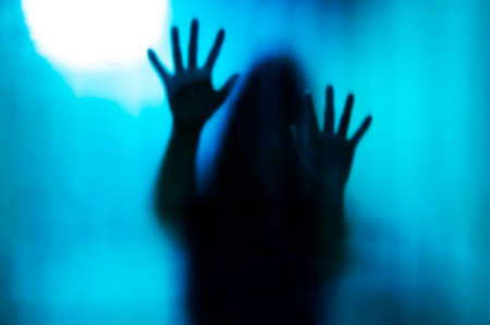 Abstract woman behind the matte glass. Blurry hand and body figure Stock Photo