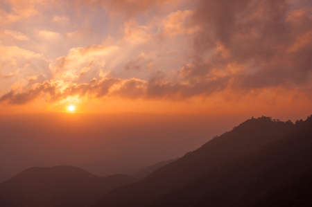 faintly visible: Sunrise silhouette mountains layer Stock Photo