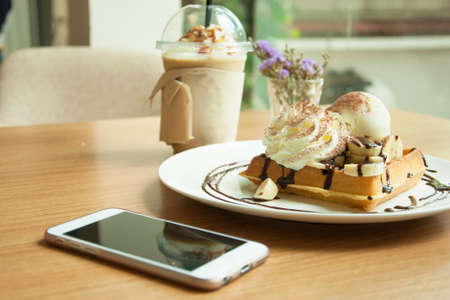 Banana and ice cream waffle chocolate syrup and coffee with mobile phone on wooden table : relax concept