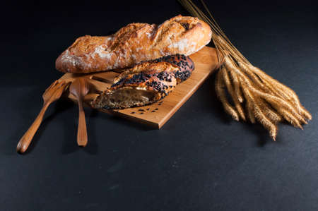 french roll: Rustic bread roll or french baguette, wheat on wooden at black background with text copy space