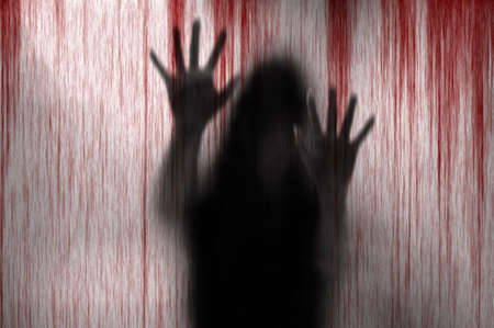 Horror woman behind the matte glass blood stain.  Blurry hand and body figure abstraction. Stock Photo
