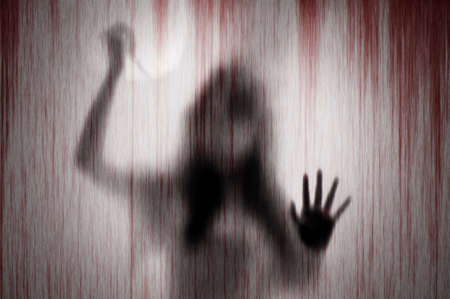 Horror shadow of woman figure with a  scissors behind the matte glass and blood stain.  Blurry abstraction concept