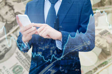 Double exposure of businessman , Financial graph and cityscape with Japanese JPY Yen and USD Dollar bank note pile background, Business and finance concept Stock Photo