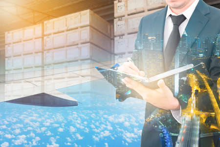 exportation: Double exposure of businessman writing notebook and business center city with blurred cargo in wooden case at warehouse and export plane aeriel background, exportation and trading concept