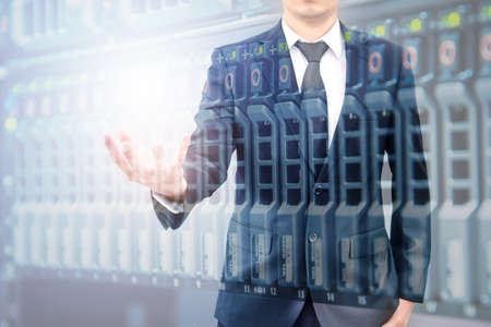 Double expoure of hand businessman and servers technology in datacenter with text copy space above empty hand