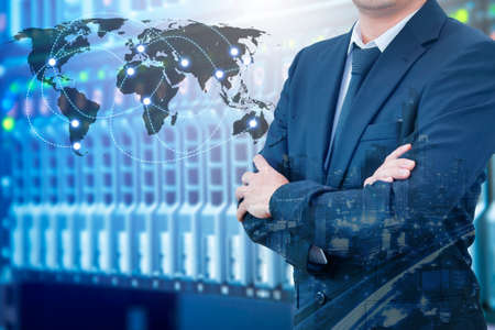 Double exposure of professional businessman standing crossed arms connecting internet with servers storage technology and connect world network in IT Business concept, element of this image furnished by NASA Foto de archivo