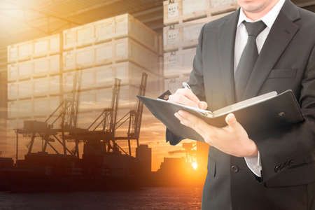 Businessman writing notebook with blurred cargo in wooden case and transportation port background, trading export abroad concept