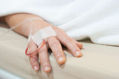 Close up a hand of middle age woman patient in hospital with saline intravenous Stock Photo