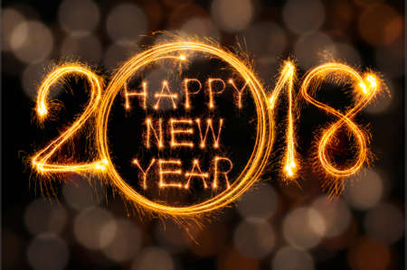 Happy new year 2017 text written with Sparkle fireworks isolated on black background Foto de archivo