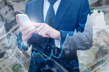 Double exposure of businessman using smart phone, Financial graph and cityscape with Japanese JPY Yen and USD Dollar bank note pile background, Business and finance concept