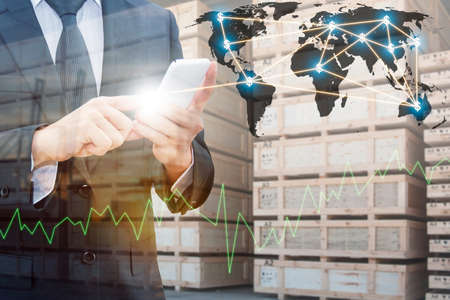 Double exposure of professional businessman using smart phone , city centre of business with blurred transportation port and distribution cargo warehouse background, Technology Transportation & Business trading concept, Standard-Bild