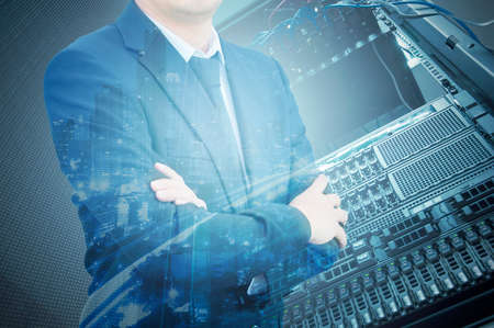 Double exposure of professional businessman with servers technology in data center and city in IT Business concept Imagens