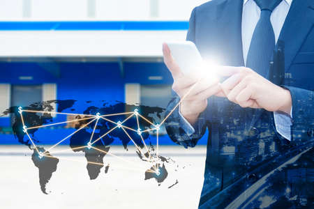 Double exposure of businessman using smart phone network connection world map  and city of business center with blurred cargo distribution warehouse background, international transportation trading business concept Stock Photo