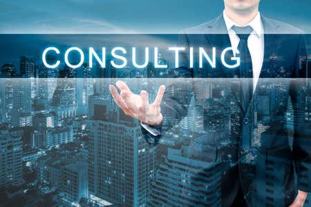 Dubbele expoure van professionele zakenman met nachtcityscape in blauwe toon greep het RAADPLEGEN van woord in bedrijfsconcept