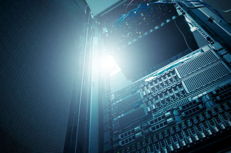 data recovery: Bottom view of rack server against neon light in datacenter with dept of field