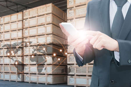 Double exposure of businessman using smart phone network connection   world map element and transportation port with blurred cargo warehouse background, international transportation trading business concept Banque d'images