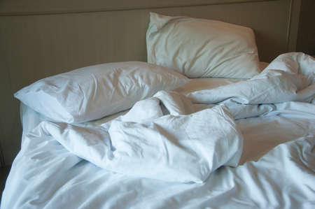 unmade: Unmade bed in hotel with warm light Stock Photo