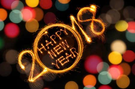 幸せな新しい年 2018 輝き花火と多重のカラフルなライト ボケ背景で書かれました。 写真素材