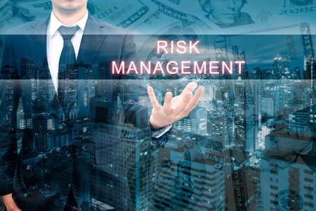 intervene: Double exposure of professional businessman with night cityscape in blue tone hold RISK MANAGEMENT word in business concept Stock Photo