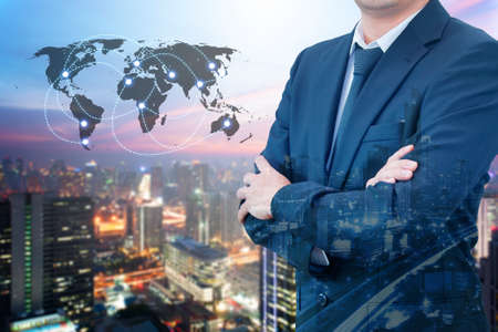 international internet: Double exposure of young handsome confident professional businessman standing crossed arms and night cityscape with modern office building background, Business & Real estate agency concept Stock Photo