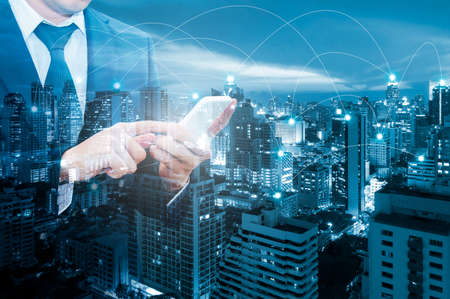 Double exposure of professional businessman connecting internet with network and city of business background  in Business / Technology / Communication and Trading concept Standard-Bild