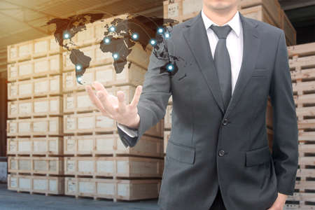 map case: Double exposure of businessman hold world map connect international network with blurred logistic transport cargo in wooden case at warehouse background for transportation and business concept Stock Photo