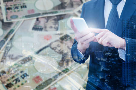 Double exposure of businessman using smart phone and city of business with Japanese JPY Yen bank note pile background, Business and finance concept