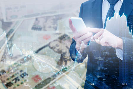 Double exposure of businessman using smart phone , Financial graph and city of business with Japanese JPY Yen bank note pile background, Business and finance concept Stock Photo