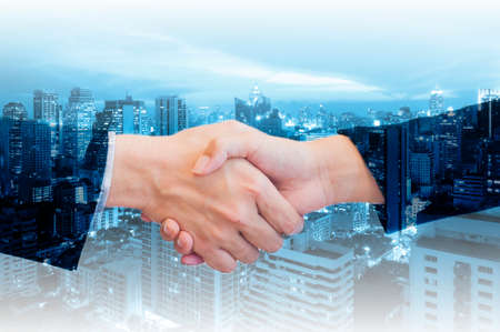 satisfies: Double exposure of businessman and businesswoman handshake with city of business in blue tone background