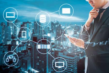 Podwójna ekspozycja zawodowych biznesmen podłączony do Internetu i sieci bezprzewodowej ze swoim inteligentnym telefonem i miasto biznesu w tle w biznesie i koncepcji technologii