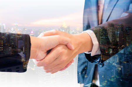 satisfies: Double exposure of businessman and businesswoman handshake agree deal with city of business in blue tone background Stock Photo