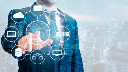 Double exposure of professional businessman connected devices with world digital technology internet and wireless network on touch screen and city of business background in business and technology concept Archivio Fotografico
