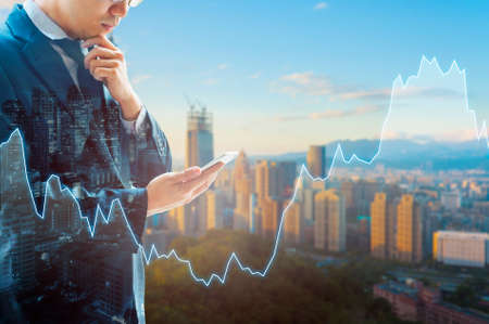 De dubbele blootstelling van professionele zakenman verbindt Internet in slimme telefoon en stad van commercieel centrum in blauwe koele toon met internationale wereld financiële grafiek Stockfoto