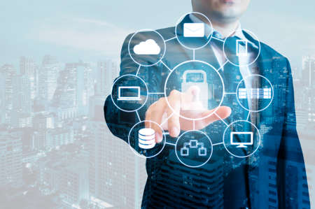 Double exposure of professional businessman touching security icon on screen connect internet and network all device with stylus pen and city of business in blue tone , business and technology concept