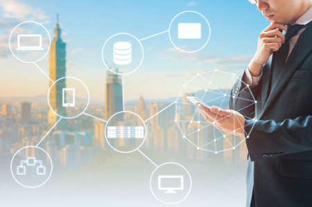 Double exposure of professional businessman connected internet and wireless network with his smart phone and city of business background in business trading and technology concept Archivio Fotografico