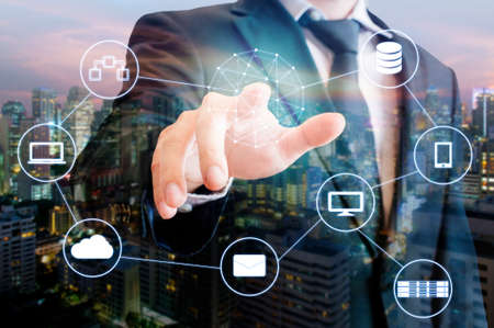 Double exposure of professional businessman touch on screen connected devices with world digital technology internet and wireless network and city of business background in business and technology concept