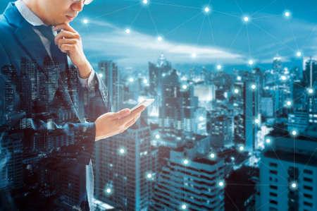 Dubbele blootstelling van professioneel zakenman verbonden Internet en draadloos netwerk met zijn slimme telefoon en stad van bedrijfsachtergrond in zaken handel en technologieconcept Stockfoto