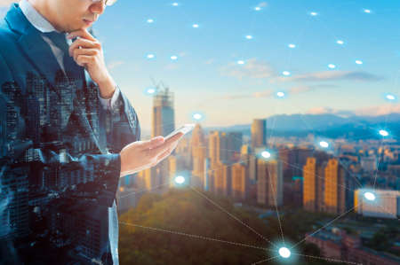 Double exposure of professional businessman connected internet and wireless network with his smart phone and city of business background in business trading and technology concept Imagens