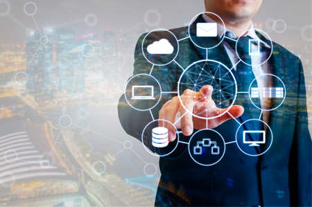 Double exposure of professional businessman connected devices with world digital technology internet and wireless network on touch screen and city of business background in business and technology concept Imagens