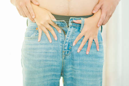 Woman unzipped jeans of man for having sex in sex concept Stock Photo - 80158212