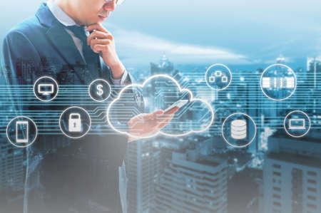 Dwoisty ujawnienie fachowego biznesmena łącząca Obłoczna technologia z internetem i siecią bezprzewodową z jego mądrze telefonem i miastem biznesowy tło w biznesowym handlu i technologii pojęciu