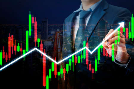 Professional businessman pointing stylus pen on candle stick chart and up trend line graph, online stock exchange trading and forex investment concept Stock Photo