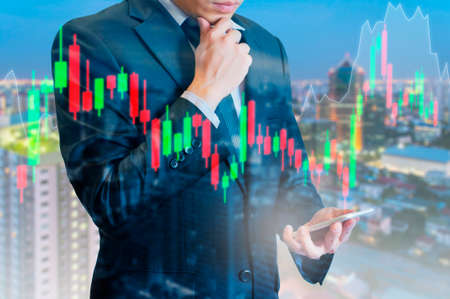 Double exposure of professional businessman analyse stock candle stick graph of stocks market on digital touch screen in business stock trading concept